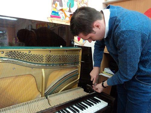 мужчина разбирает пианино